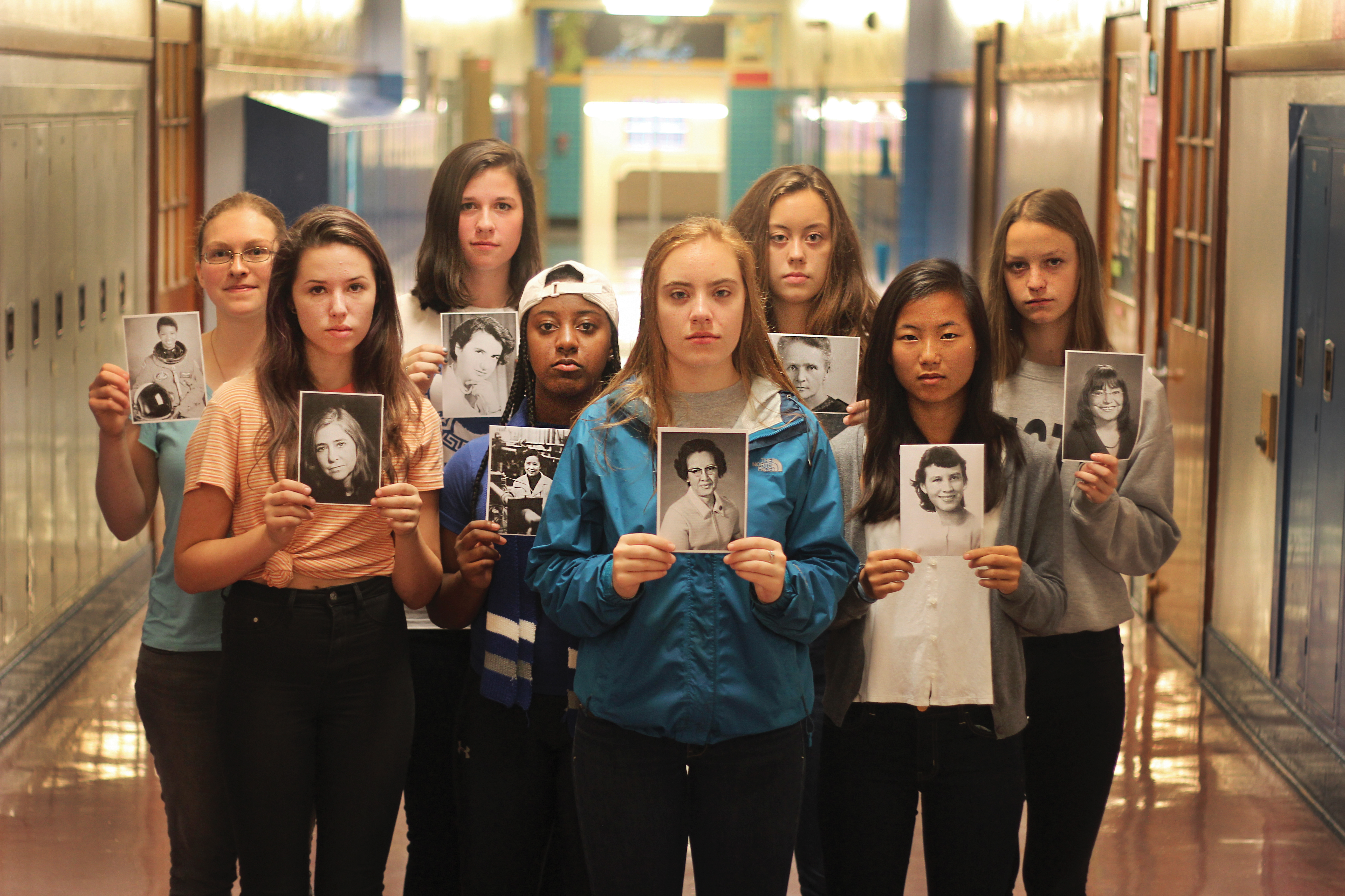 "Girls at Grant High School say many science classes don't feel welcoming to them because of their gender. These students — all with a high level of interest in the sciences — hold photos of the faces of prominent women in the field. They are (from left to right): senior Lillian Peters, holding a picture of astronaut Mae C. Jemison; sophomore Siena Lesher, with computer scientist Margaret Hamilton; junior Megan Hurley, with chemist and DNA expert Rosalind Franklin; senior Jehdah Walker, with Chien Shiung Wu, known as the ""First Lady of Physics;"" junior Emma Findling, with Katherine Johnson, a noted physicist and mathematician; junior Kirsten Rydell, with Marie Curie, the famous physicist and chemist; junior Quinn McGranaghan, with microbiologist Esther Lederberg; and senior Thea Foulk, with Lydia Villa-Komaroff, a molecular biologist."