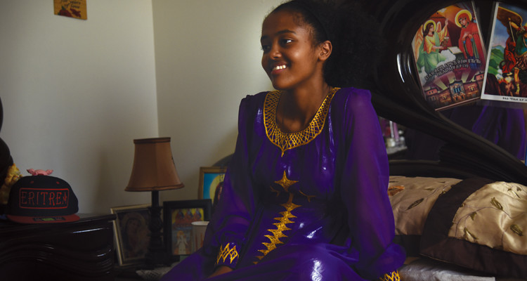 Asghedom sits to relax after an all-day annual church ceremony. Her room is decorated with pictures of Eritrea as a means of holding onto past memories.